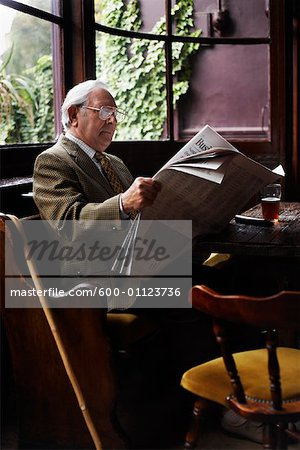 Man Reading Newspaper in Pub Stock Photo - Premium Royalty-Free, Image code: 600-01123736