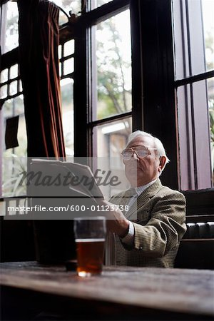 Man Reading Newspaper in Pub Stock Photo - Premium Royalty-Free, Image code: 600-01123738