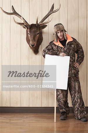 Hunter Leaning on Sign Stock Photo - Premium Royalty-Free, Image code: 600-01124345