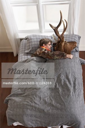 Hunter Sleeping with Deer Head Stock Photo - Premium Royalty-Free, Image code: 600-01124359