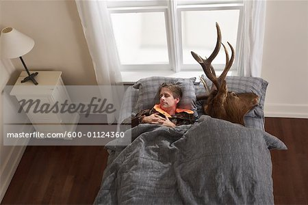 Hunter Sleeping with Deer Head Stock Photo - Premium Royalty-Free, Image code: 600-01124360