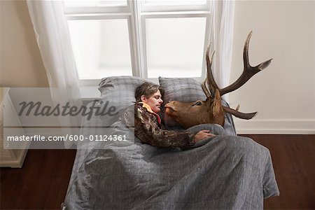 Hunter Sleeping with Deer Head Stock Photo - Premium Royalty-Free, Image code: 600-01124361
