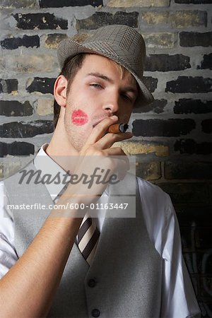 Portrait of Man With Lipstick Mark on Cheek, Smoking a Cigar Stock Photo - Premium Royalty-Free, Image code: 600-01163447