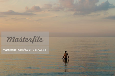 Man Standing in Ocean Stock Photo - Premium Royalty-Free, Image code: 600-01173584