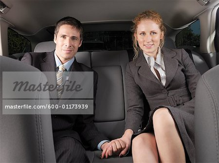 Man and Woman Holding Hands in Back of Car Stock Photo - Premium Royalty-Free, Image code: 600-01173939