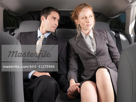 Man and Woman Holding Hands in Back of Car Stock Photo - Premium Royalty-Free, Image code: 600-01173940