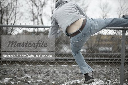 Man Climbing over Fence Stock Photo - Premium Royalty-Free, Image code: 600-01184408
