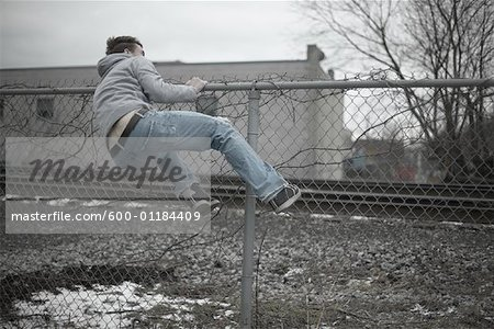Man Climbing over Fence Stock Photo - Premium Royalty-Free, Image code: 600-01184409