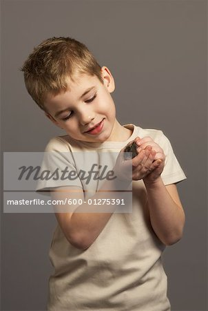 Little Boy Holding Hamster Stock Photo - Premium Royalty-Free, Image code: 600-01275391