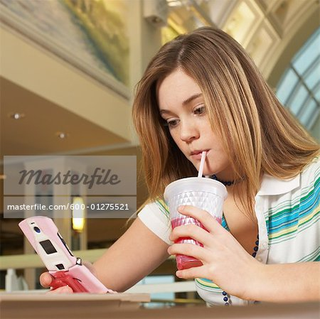 Teenager Looking at Cell Phone Stock Photo - Premium Royalty-Free, Image code: 600-01275521