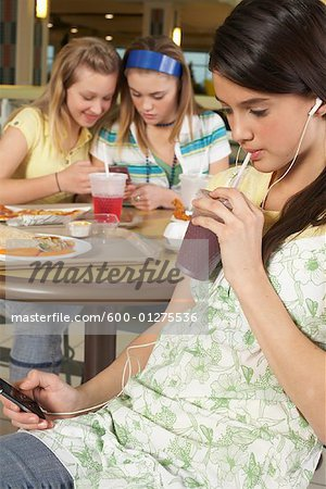 Teenager Listening to MP3 Player, Friends in Background Stock Photo - Premium Royalty-Free, Image code: 600-01275536