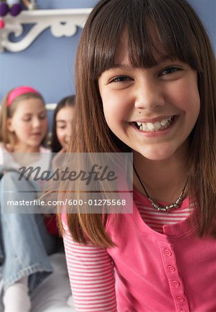 Close-up of Girl with Friends in Background Stock Photo - Premium Royalty-Free, Image code: 600-01275568
