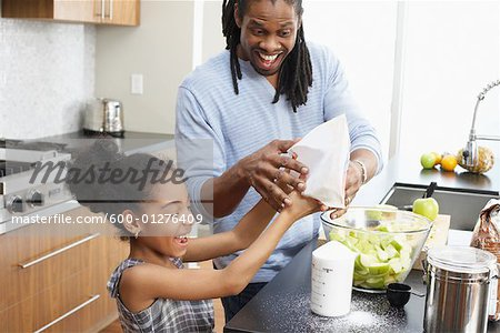 Father and Daughter Making Applesauce in Kitchen Stock Photo - Premium Royalty-Free, Image code: 600-01276409