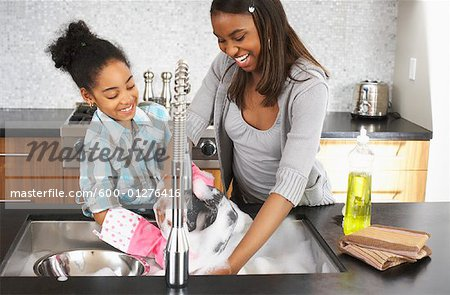 Sisters Washing Dishes Stock Photo - Premium Royalty-Free, Image code: 600-01276416