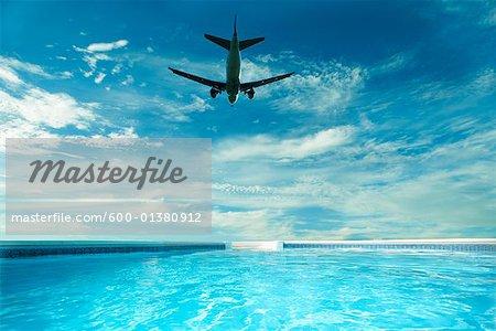 Plane Flying over Backyard Pool