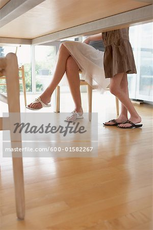 View of People's Legs Under Table Stock Photo - Premium Royalty-Free, Image code: 600-01582267