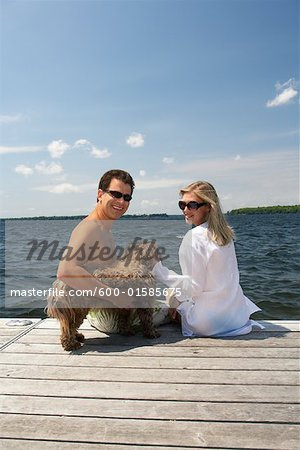 Couple on Dock With Dog Stock Photo - Premium Royalty-Free, Image code: 600-01585675