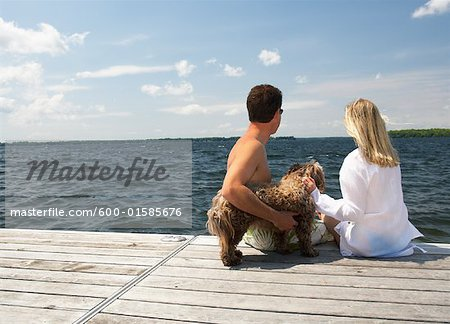 Couple on Dock With Dog Stock Photo - Premium Royalty-Free, Image code: 600-01585676