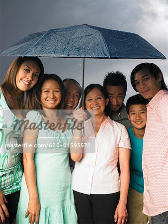 Family Standing together Under Umbrella Stock Photo - Premium Royalty-Free, Image code: 600-01593572