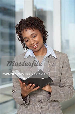 Businesswoman Reading Appointment Book Stock Photo - Premium Royalty-Free, Image code: 600-01613913