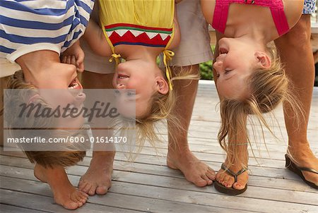 Parents Holding Children Upside Down Stock Photo - Premium Royalty-Free, Image code: 600-01614170
