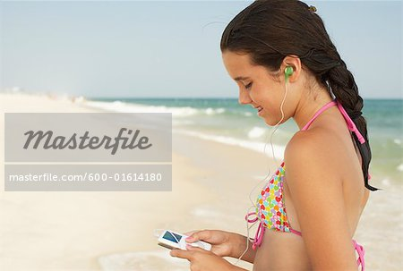 Girl on Beach With Mp3 Player Stock Photo - Premium Royalty-Free, Image code: 600-01614180