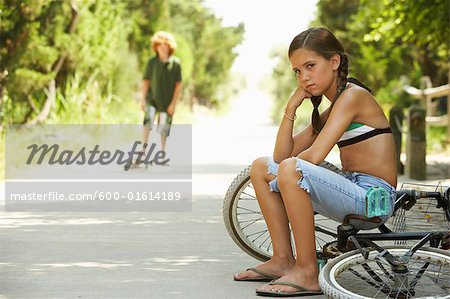 Little Girl Sitting on Bike Looking Angry Stock Photo - Premium Royalty-Free, Image code: 600-01614189