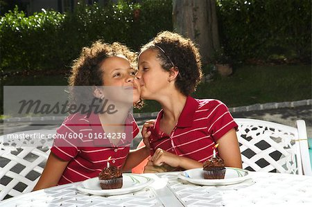 Girl Kissing Sister on Cheek Stock Photo - Premium Royalty-Free, Image code: 600-01614238