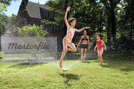 Family playing in backyard with sprinkler Stock Photo - Premium Royalty-Free, Image code: 600-01614307