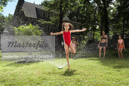Family playing in backyard with sprinkler Stock Photo - Premium Royalty-Free, Image code: 600-01614308