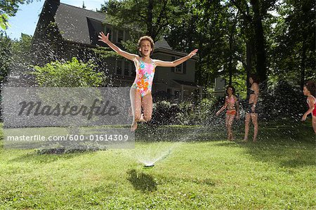 Family playing in backyard with sprinkler Stock Photo - Premium Royalty-Free, Image code: 600-01614309