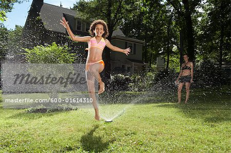 Family playing in backyard with sprinkler Stock Photo - Premium Royalty-Free, Image code: 600-01614310