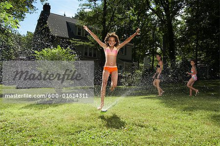 Family playing in backyard with sprinkler Stock Photo - Premium Royalty-Free, Image code: 600-01614311