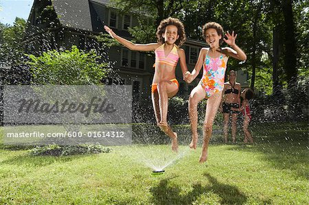 Family playing in backyard with sprinkler Stock Photo - Premium Royalty-Free, Image code: 600-01614312