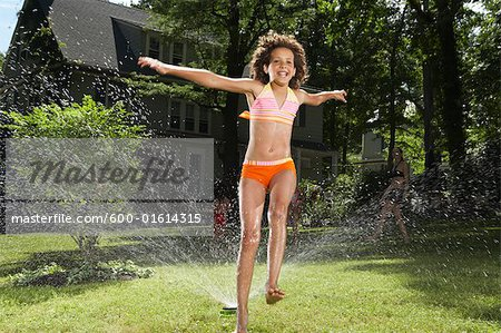 Family playing in backyard with sprinkler Stock Photo - Premium Royalty-Free, Image code: 600-01614315