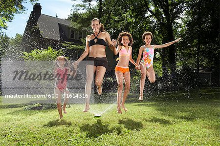 Family playing in backyard with sprinkler Stock Photo - Premium Royalty-Free, Image code: 600-01614316