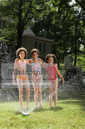 Family playing in backyard with sprinkler Stock Photo - Premium Royalty-Free, Image code: 600-01614317