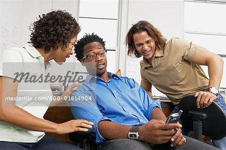 Coworkers looking at cell phone Stock Photo - Premium Royalty-Free, Image code: 600-01614904