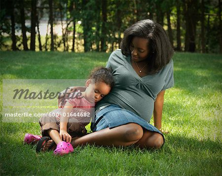 Mother and Daughter Sitting in Yard Stock Photo - Premium Royalty-Free, Image code: 600-01644682