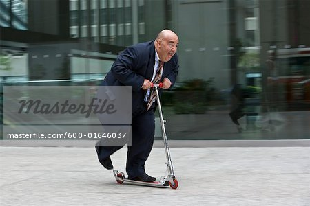 Businessman on Scooter Stock Photo - Premium Royalty-Free, Image code: 600-01646037