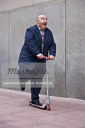 Businessman on Scooter Stock Photo - Premium Royalty-Free, Image code: 600-01646038
