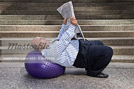Businessman with Exercise Ball and Newspaper Stock Photo - Premium Royalty-Free, Image code: 600-01646040