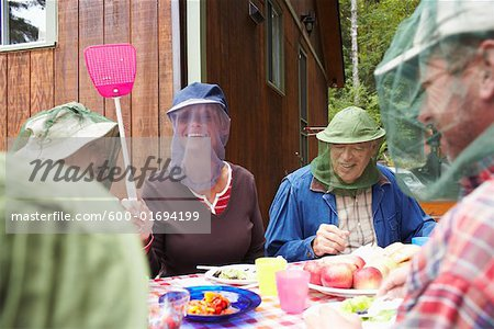 Family around Outdoor Table with Insect Masks Stock Photo - Premium Royalty-Free, Image code: 600-01694199