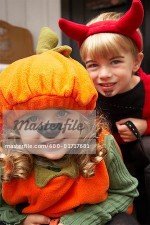 Portrait of Girl Dressed-up as Pumpkin and Boy Dressed-up as Devil Stock Photo - Premium Royalty-Free, Image code: 600-01717681