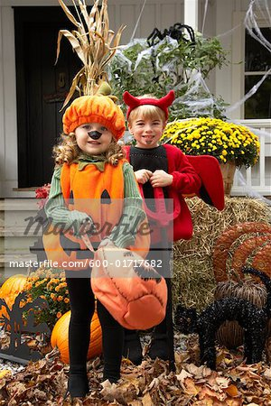 Portrait of Girl Dressed-up as Pumpkin and Boy Dressed-up as Devil Stock Photo - Premium Royalty-Free, Image code: 600-01717682