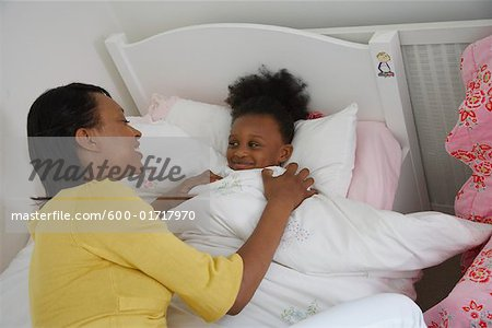Mother Tucking Daughter into Bed Stock Photo - Premium Royalty-Free, Image code: 600-01717970