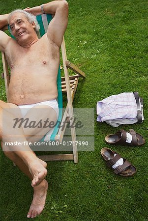 Man Sitting in Lawn Chair in His Underwear Stock Photo - Premium Royalty-Free, Image code: 600-01717990