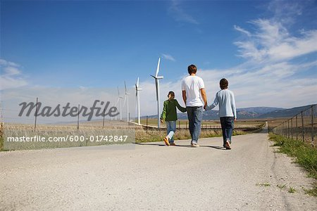 Father and Children Walking on Rural Road, next to Wind Turbines Stock Photo - Premium Royalty-Free, Image code: 600-01742847