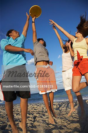 Friends Playing Frisbee on Beach Stock Photo - Premium Royalty-Free, Image code: 600-01838215
