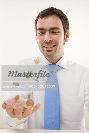Man Tossing Coins Stock Photo - Premium Royalty-Free, Image code: 600-02010039